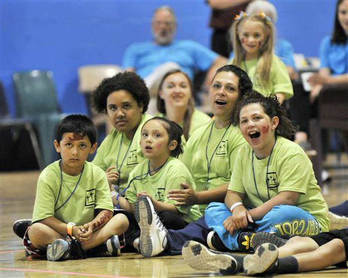 FOR USE MONDAY, JULY 4, AND THEREAFTER- This photo taken June 4, 2016, shows Inmate Tara Vallejo of Lansing, second from right, sits with her children, from left, Giovanni Vallejo, 7, Destiny Coffman, 13, Serenity Vallejo, 6, and TaLeesa Coffman, 9, while they watch a strong man bend a horse shoe at the Women's Huron Valley Correctional Facility in Ypsilanti, Mich. Children get to spend a whole day with their mothers who are incarcerated in a program called One Day with God camp provided by Forgiven Ministry. (Robin Buckson/Detroit News via AP)