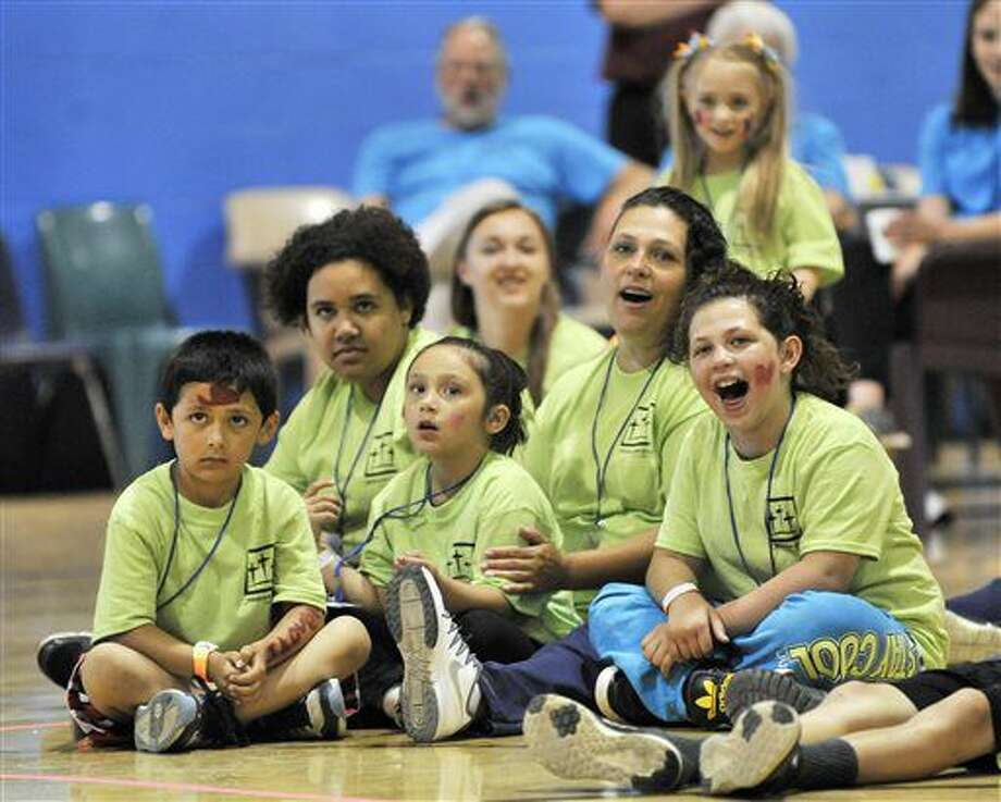 FOR USE MONDAY, JULY 4, AND THEREAFTER- This photo taken June 4, 2016, shows Inmate Tara Vallejo of Lansing, second from right, sits with her children, from left, Giovanni Vallejo, 7, Destiny Coffman, 13, Serenity Vallejo, 6, and TaLeesa Coffman, 9, while they watch a strong man bend a horse shoe at the Women's Huron Valley Correctional Facility in Ypsilanti, Mich. Children get to spend a whole day with their mothers who are incarcerated in a program called One Day with God camp provided by Forgiven Ministry. (Robin Buckson/Detroit News via AP) Photo: Robin Buckson