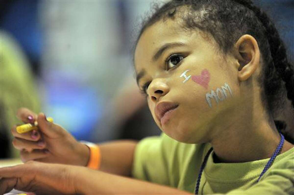FOR USE MONDAY, JULY 4, AND THEREAFTER - This photo taken June 4, 2016, shows Kle'Shaya Jamison, 7, of Pontiac, Mich., colors while she waits to get to see her mom at the Women's Huron Valley Correctional Facility in Ypsilanti, Mich. on June 4, 2016. Children get to spend a whole day with their mothers who are incarcerated in a program called One Day with God camp provided by Forgiven Ministry. (Robin Buckson/Detroit News via AP)