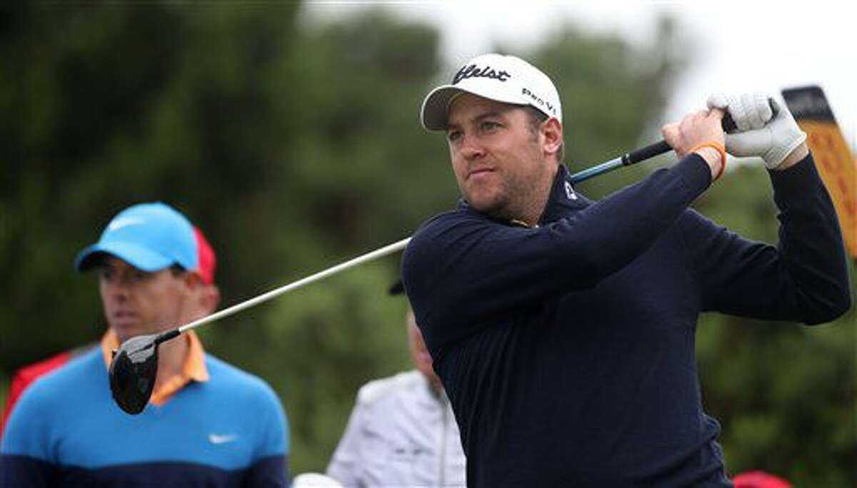Matthew Southgate of England, right, plays his shot on the 12th tee, watched by Rory McIlroy of Northern Ireland, during a practice round for the British Open Golf Championships at the Royal Troon Golf Club in Troon, Scotland, Tuesday, July 12, 2016. (AP Photo/Peter Morrison)