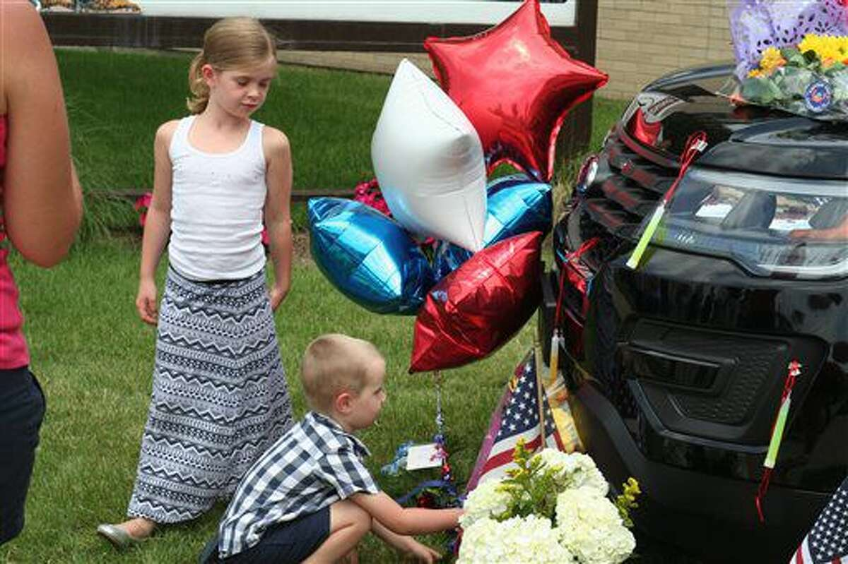 Lily and Keegan Goff, the children of Berrien County Sheriff SWAT team DeputyJustin Goff, place flowers Tuesday, July 12, 2016, at a memorial for slain court officers Joe Zangaro and Ron Kienzle in St. Joseph, Mich.. Deputy Goff was one of the first responders when the fatal shootings at the Berrien County Courthouse occurred Monday. (John Matuszak/The Herald-Palladium via AP)