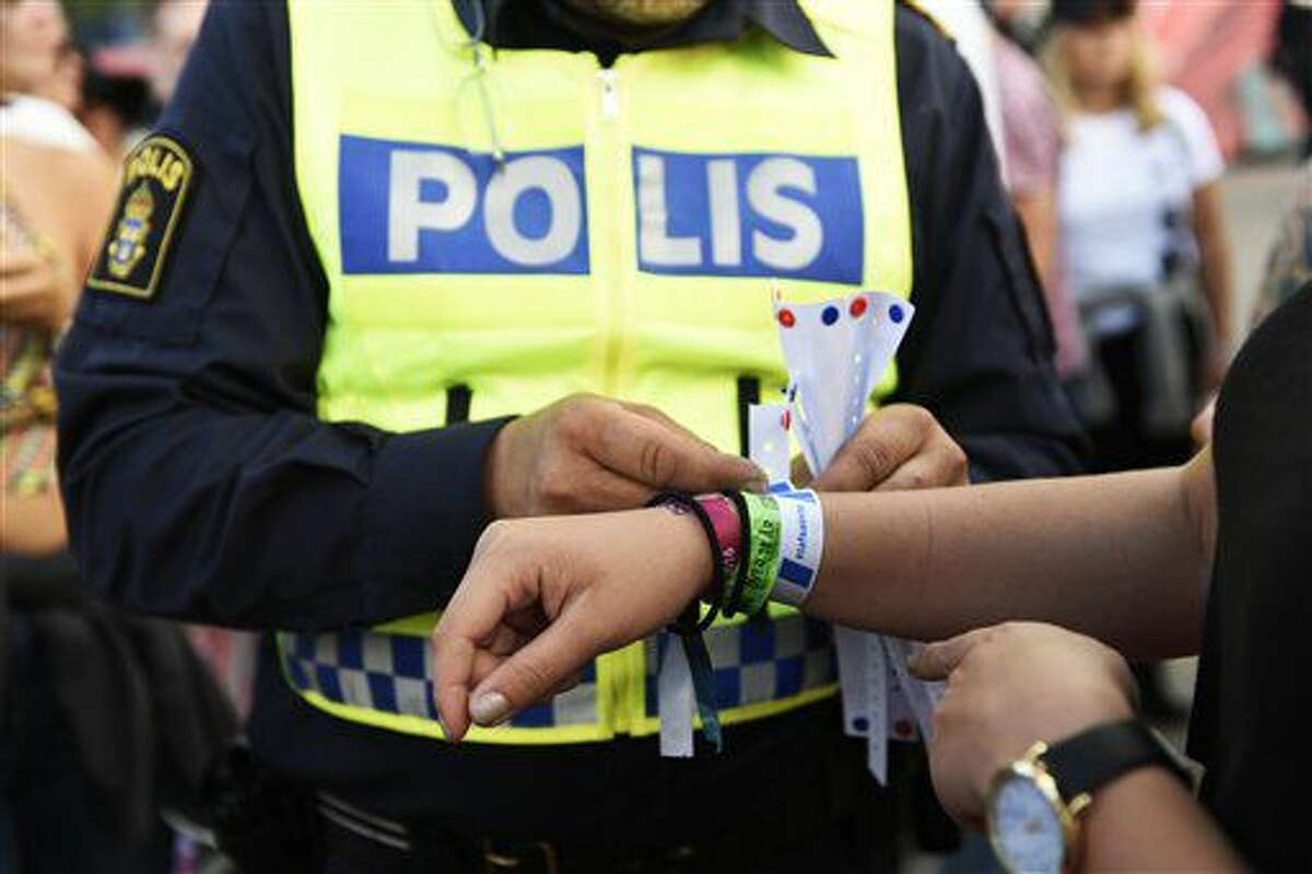 In this photo dated Friday July 1, 2016, A police officer attaches a bracelet with the text #tafsainte, meaning don't grope, to a visitor's wrist at the Bravalla Festival in Norrkoping, Sweden, on Friday July 1, 2016. Swedish police told the media Tuesday July 5, 2016, that they are investigating five cases of alleged rape and more than a dozen suspected sexual assaults committed at the Bravalla Festival over last weekend. (Izabelle Nordfjell / TT via AP)