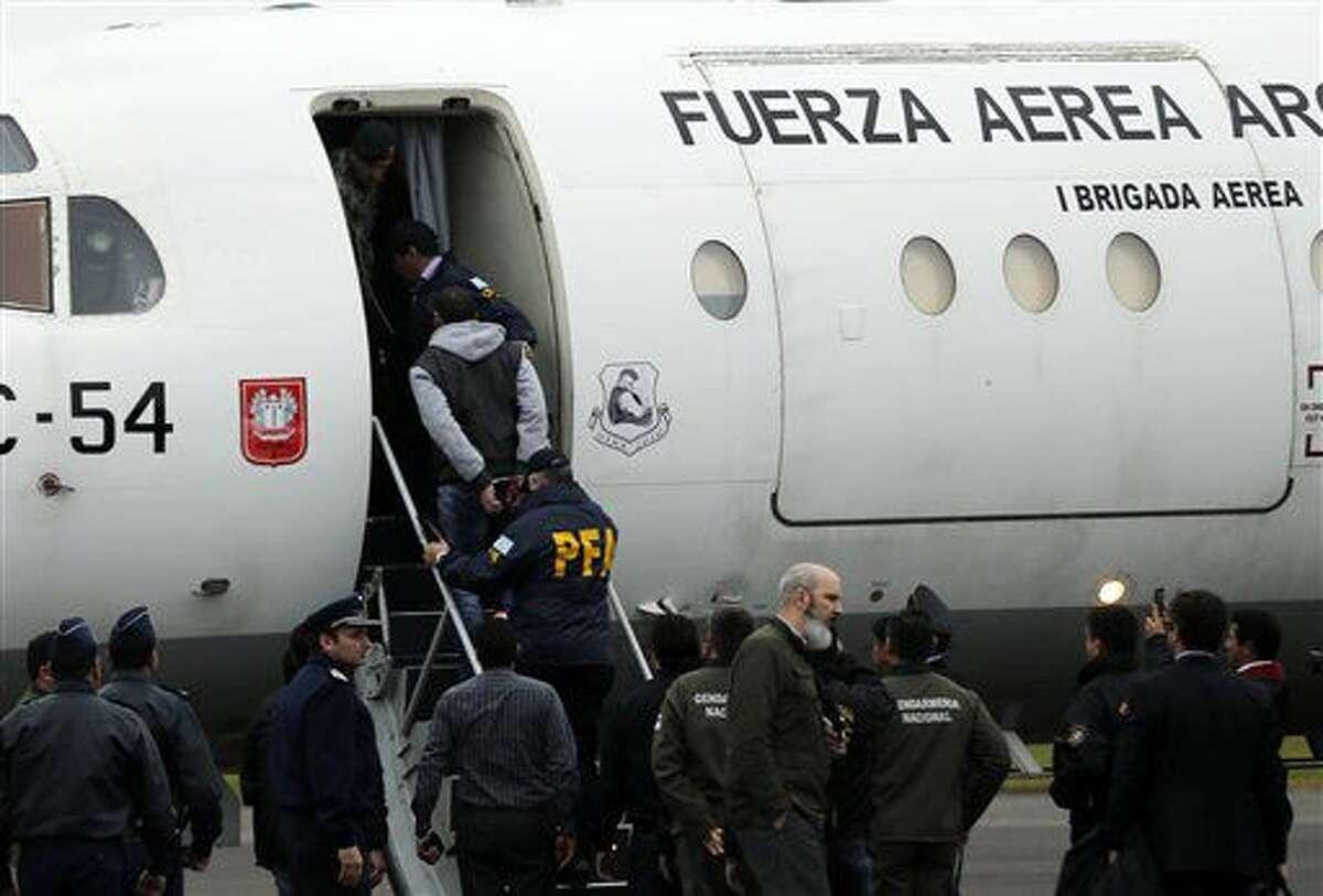 El argentino Ibar Perez Corradi, en las escalerillas, es escoltado por la policía hacia un avión de la fuerza aérea en el aeropuerto militar de Asunción, el martes 15 de julio de 2016. (AP Foto/Jorge Saenz)