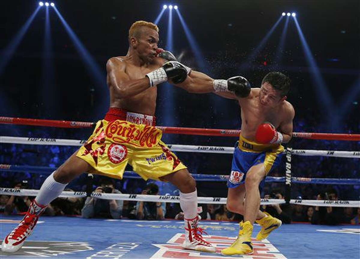 File-This March 7, 2015, file photo shows China's double Olympic gold medalist Zou Shiming, right, and Thailand's Amnat Ruenroeng exchanging punches during their IBF flyweight title belt boxing match at the Venetian Macao in Macau. Ruenroeng and Cameroon's Hassan N'Dam are the most prominent professional boxers trying to take advantage of the International Boxing Association's decision to allow pros to compete for Olympic spots. (AP Photo/Kin Cheung, File)