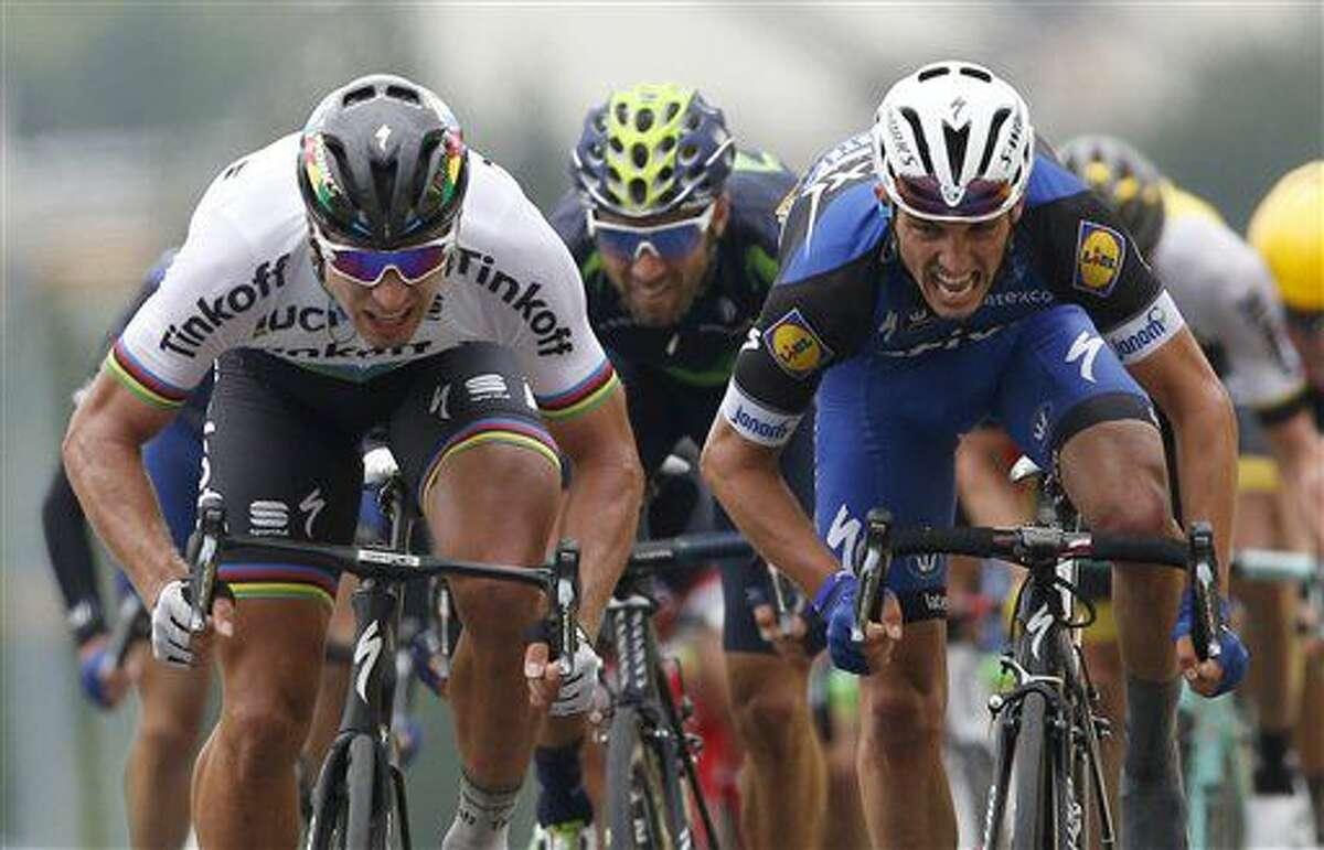 El eslovaco Peter Sagan, izquierda, cruza la meta al frente del primero pelotón para vencer al francés Julian Alaphilippe, derecha, y al español Alejandro Valverde al llevarse la segunda etapa del Tour de Francia, un tramo de 183 kilómetros (113,7 millas) de Saint-Lo a Cherbourg-en-Cotentin, Francia, el domingo 3 de julio de 2016. (AP Foto/Christophe Ena)