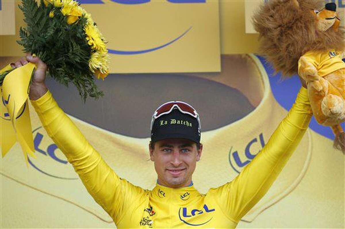 El eslovaco Peter Sagan festeja desde el podio con la camiseta amarilla de líder tras llevarse la segunda etapa del Tour de Francia, un tramo de 183 kilómetros (113,7 millas) de Saint-Lo a Cherbourg-en-Cotentin, Francia, el domingo 3 de julio de 2016. (AP Foto/Peter Dejong)