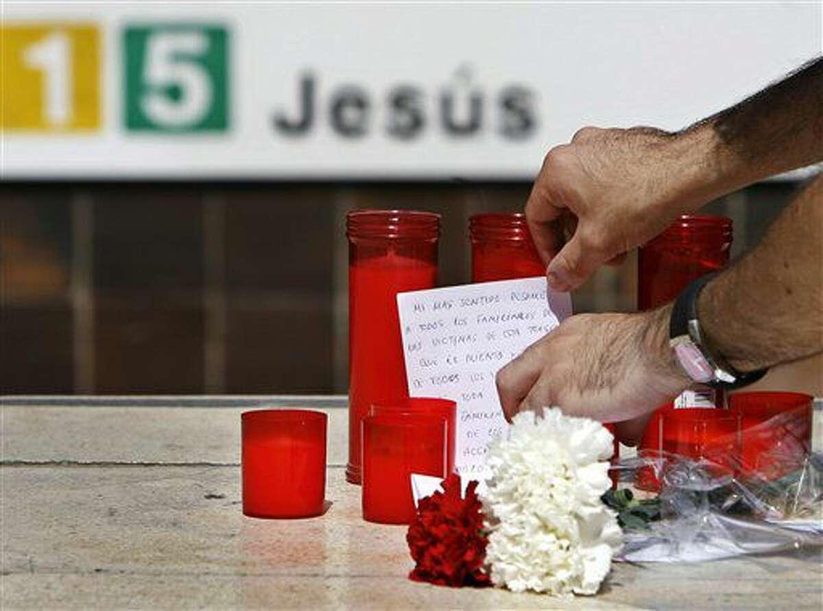 ARCHIVO - En esta foto del 4 de julio de 2006, una persona deja un mensaje entre unas velas a la entrada de la estación del metro Jesús, en Valencia, donde un día antes un tren se descarriló. Decenas de personas rindieron homenaje el domingo 3 de julio de 2016 a las víctimas del accidente que dejó 43 muertos y 47 heridos. (AP Foto/Fernando Bustamante, Archivo)
