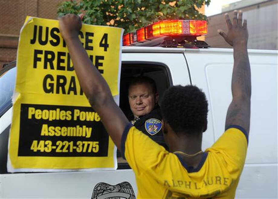 """Melvin Townes, of Baltimore, stands with a """"Justice 4 Freddie Gray"""" sign in front of a police officer during a protest Friday, July 8, 2016, in Baltimore. (Caitlin Few/The Baltimore Sun via AP) Photo: Caitlin Few"""