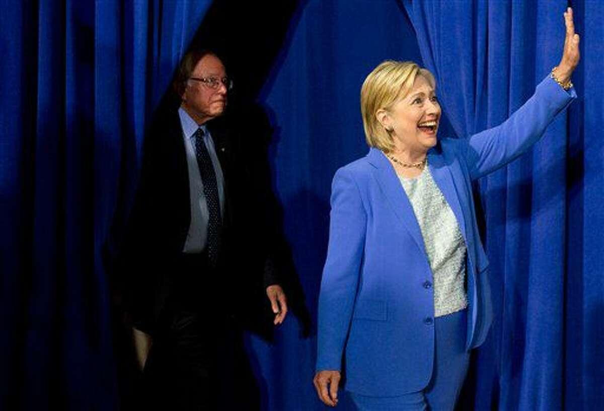La aspirante demócrata a la Casa Blanca, Hillary Clinton, seguida del senador Bernie Sanders, saluda a la multitud a la llegada de ambos a un acto político en Portsmouth, New Hampshire, el martes 12 de julio de 2016. Sanders manifestó en el lugar su apoyo a Clinton para presidenta. (AP Foto/Andrew Harnik)