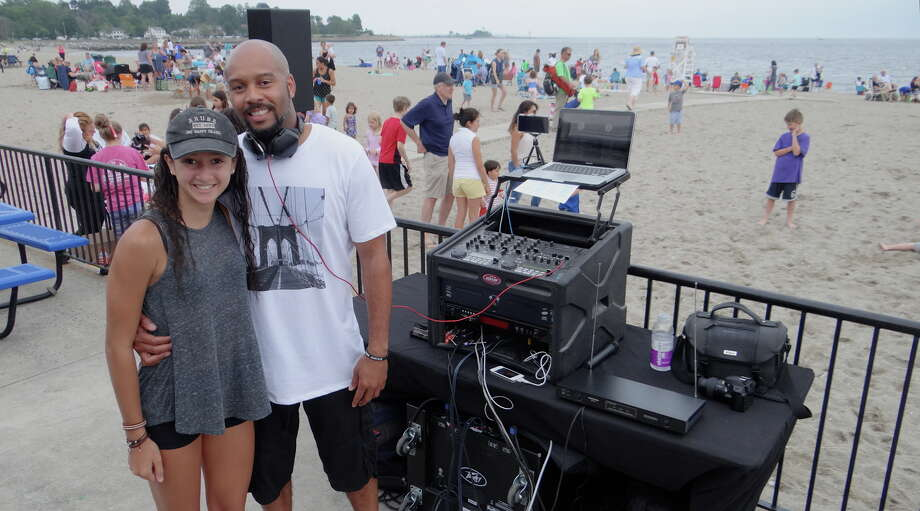 DJ Marvin Parsons and his daughter, Jordan, 15, coordinating the music portion of the Sand Jam/Movie Night at Jennings Beach Friday evening. Photo: Mike Lauterborn / For Hearst Connecticut Media / Fairfield Citizen
