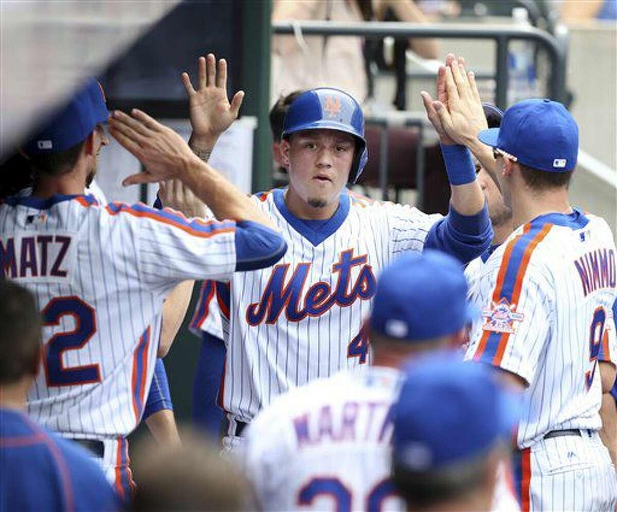 El venezolano Wilmer Flores, de los Mets de Nueva York, es felicitado por sus compañeros en la cueva, luego de anotar en el duelo ante los Cachorros de Chicago, el domingo 3 de julio de 2016 (AP Foto/Seth Wenig)