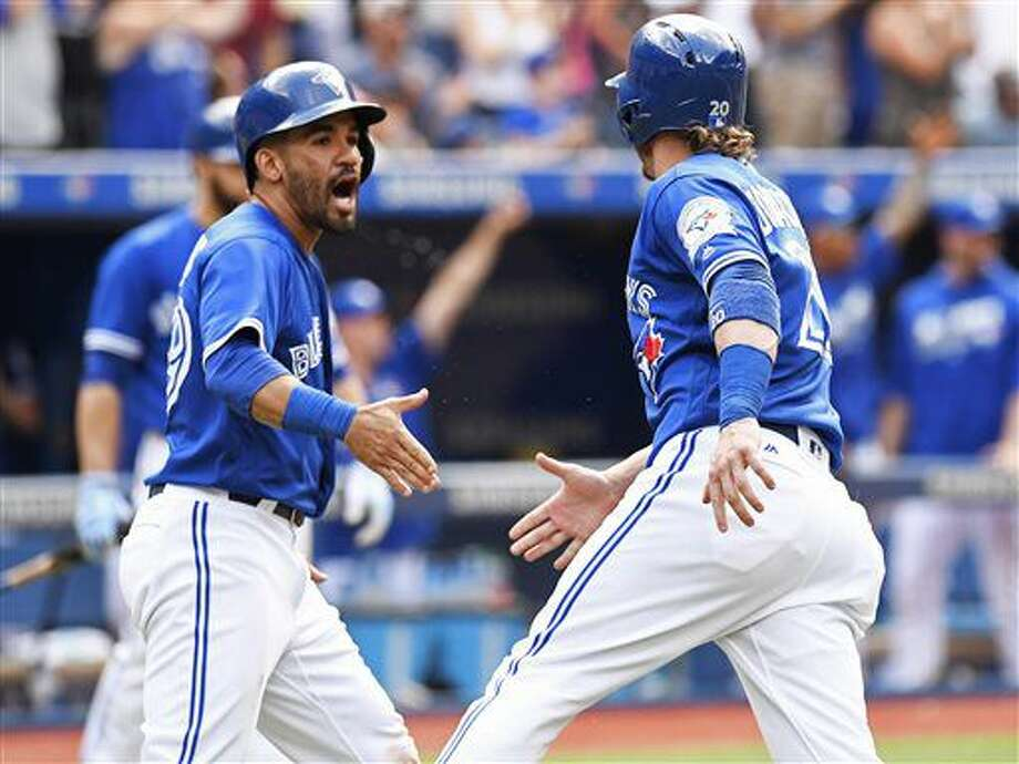 Toronto Blue Jays' Josh Donaldson, right, and Devon Travis celebrate after they scored on a double by Michael Saunders against the Cleveland Indians during eighth-inning baseball game action, in Toronto, Saturday, July 2, 2016. (Frank Gunn/The Canadian Press via AP) Photo: Frank Gunn