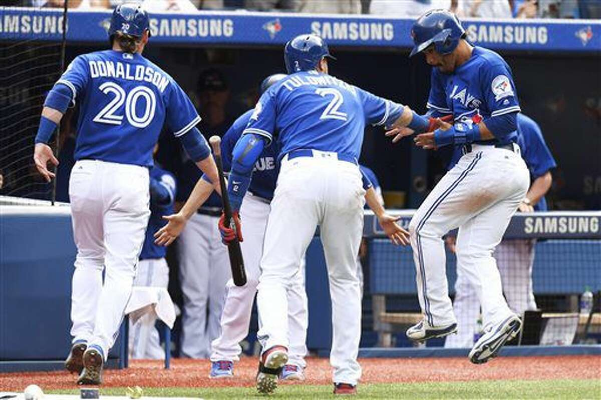 Toronto Blue Jays' Troy Tulowitzki, center, congratulates Josh Donaldson, left, and Devon Travis after they scored on a double by Michael Saunders against the Cleveland Indians during eighth-inning baseball game action, in Toronto, Saturday, July 2, 2016. (Frank Gunn/The Canadian Press via AP)