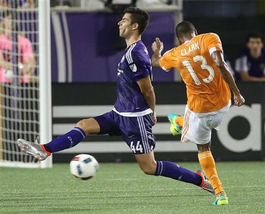 Houston Dynamo's Ricardo Clark (13) kicks a goal attempt past Orlando City's David Mateos during an MLS soccer game in Orlando, Fla., Friday, July 8, 2016. (Stephen M. Dowell/Orlando Sentinel via AP)