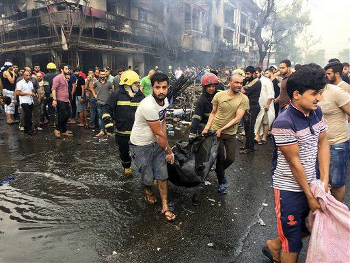 Bomberos y civiles iraquíes trasladan los cuerpos de víctimas de un auto bomba en una zona comercial del vecindario de Karada, en Bagdad, Irak, el 3 de julio de 2016. (AP Foto/Khalid Mohammed)