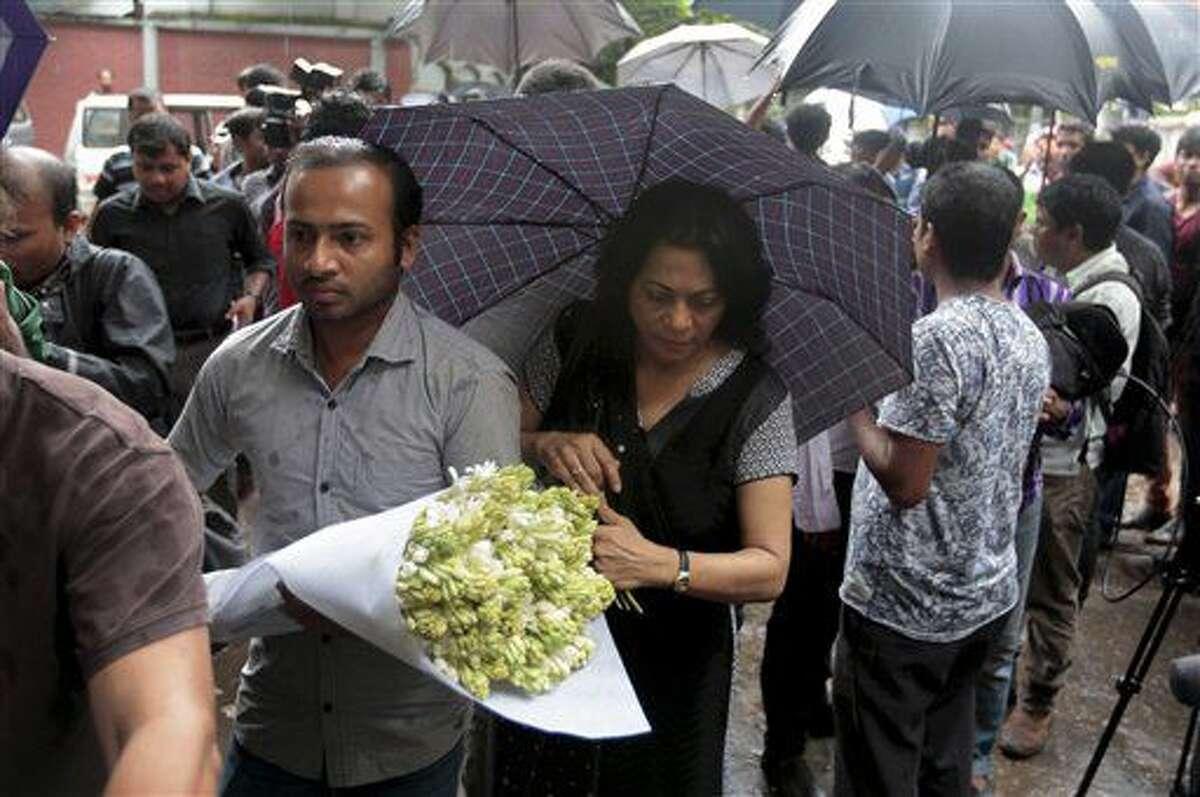 Varias personas depositas flores en señal de respeto a los fallecidos en el Holey Artisan Bakery en la zona de Gulshan, en la capital de Bangladesh, Daca, el 3 de julio de 2016. El asalto de extremistas a un restaurante del barrio diplomático de Daca, donde tomaron doceas de rehenes, supone una escalada en la violencia insurgente en un país de mayoría musulmana. (AP Foto)