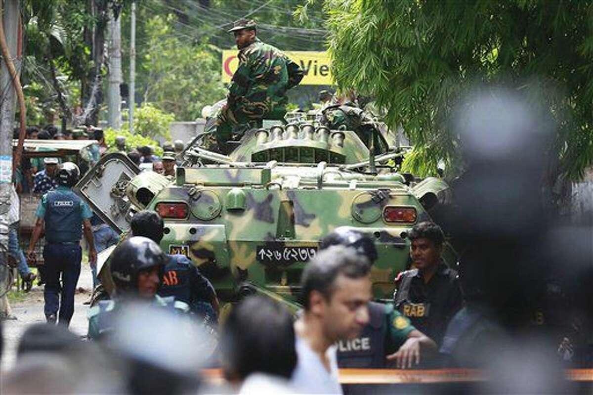Soldados de Bangladesh y personal de seguridad, sentadoa sobre carros de combate mientras acordonan una zona próxima a un restaurante popular entre los extranjeros después de que insurgentes armados tomaran docenas de rehenes, en el barrio diplomático de la capital del país, Daca, el 2 de julio de 2016. (AP Foto)