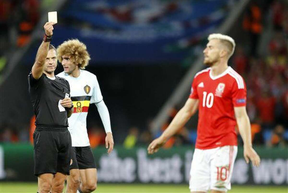 Referee Damir Skomina, left, books Wales' Aaron Ramsey, right, during the Euro 2016 quarterfinal soccer match between Wales and Belgium, at the Pierre Mauroy stadium in Villeneuve d'Ascq, near Lille, France, Friday, July 1, 2016. (AP Photo/Frank Augstein)