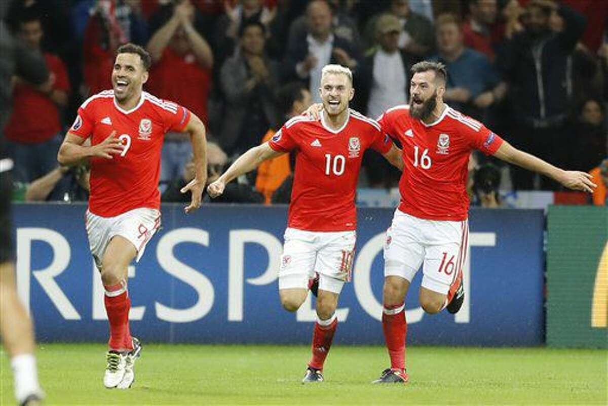Wales' Hal Robson Kanu, Aaron Ramsey and oe Ledley, from left, celebrate after Robson Kanu scored his side's second goal during the Euro 2016 quarterfinal soccer match between Wales and Belgium, at the Pierre Mauroy stadium in Villeneuve d'Ascq, near Lille, France, Friday, July 1, 2016. (AP Photo/Frank Augstein)