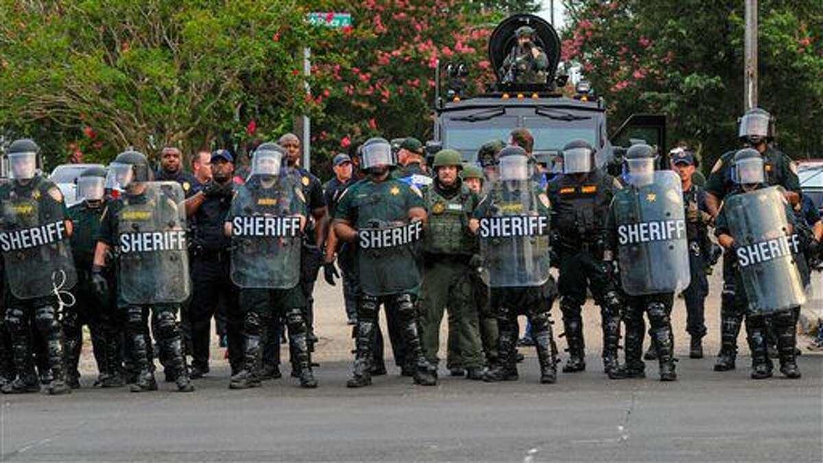 Police officers watch protesters gathering against another group of protesters in Baton Rouge, La., Sunday, July 10, 2016. Police officers responded to reports that protesters were en route to block Interstate 10 and prevent another group of protesters from marching. (Scott Clause/The Daily Advertiser via AP)