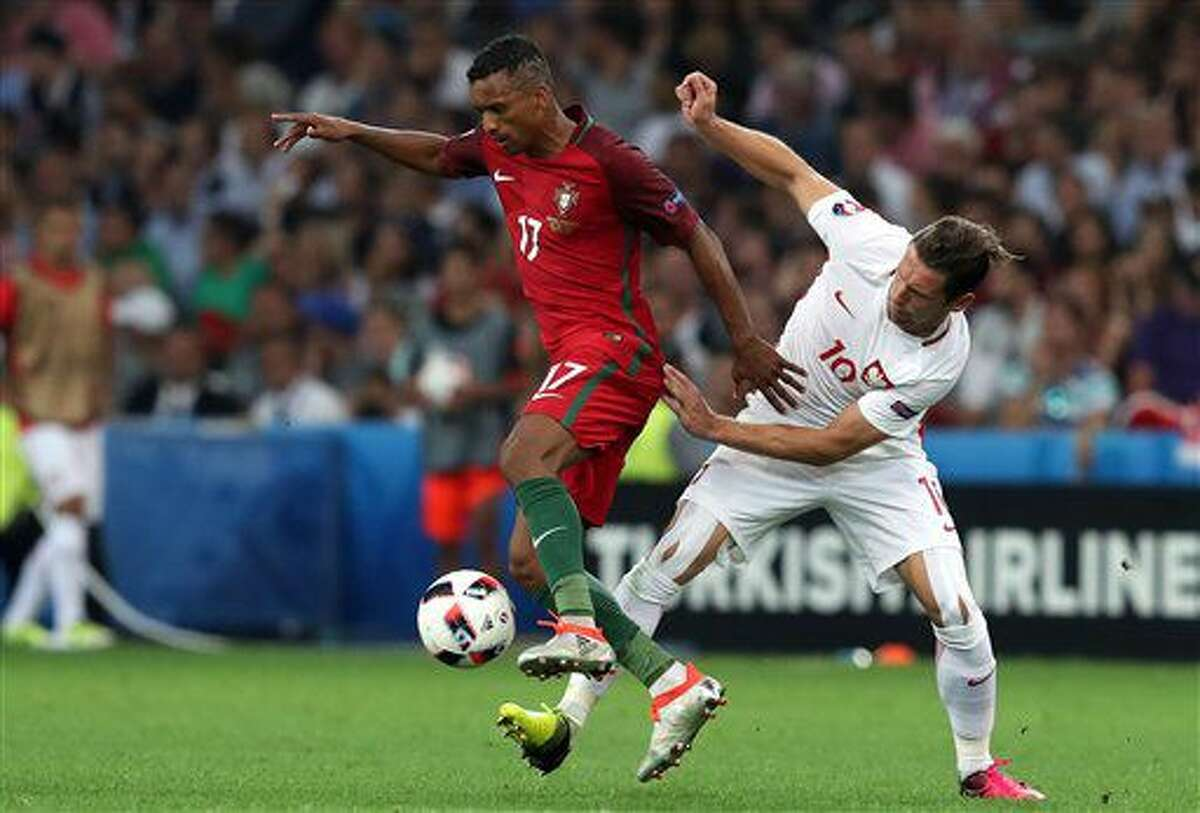 Portugal's Nani, left, fights for the ball with Poland's Grzegorz Krychowiak during the Euro 2016 quarterfinal soccer match between Poland and Portugal, at the Velodrome stadium in Marseille, France, Thursday, June 30, 2016. (AP Photo/Thanassis Stavrakis)