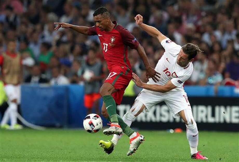 Portugal's Nani, left, fights for the ball with Poland's Grzegorz Krychowiak during the Euro 2016 quarterfinal soccer match between Poland and Portugal, at the Velodrome stadium in Marseille, France, Thursday, June 30, 2016. (AP Photo/Thanassis Stavrakis) Photo: Thanassis Stavrakis