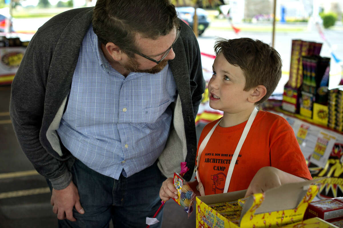 BRITTNEY LOHMILLER   blohmiller@mdn.net Raully Donahue, left, and his son, 8-year-old Calvin Donahue, both of Midland, look at different fireworks for sale in the TNT Fireworks tent at Meijer parking lot on Thursday.