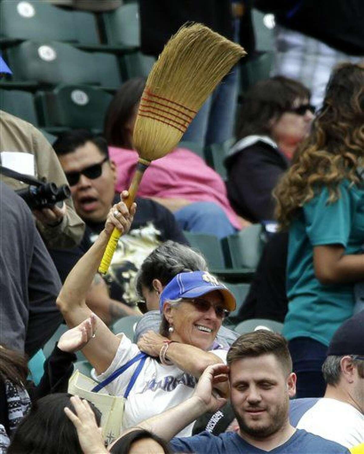 Una seguidora de los Marineros de Seattle muestra una escoba, en el duelo en que ese equipo completó una barrida sobre los Orioles de Baltimore, el domingo 3 de julio de 2016 (AP Foto/Ted S. Warren)
