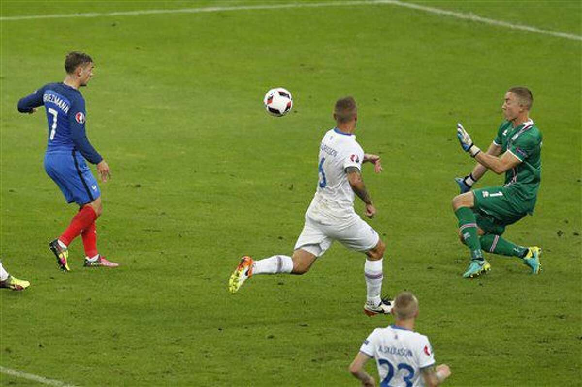 France's Antoine Griezmann, left, kicks to score his side's fourth goal past Iceland goalkeeper Hannes Halldorsson, right, during the Euro 2016 quarterfinal soccer match between France and Iceland, at the Stade de France in Saint-Denis, north of Paris, France, Sunday, July 3, 2016. (AP Photo/Michael Sohn)