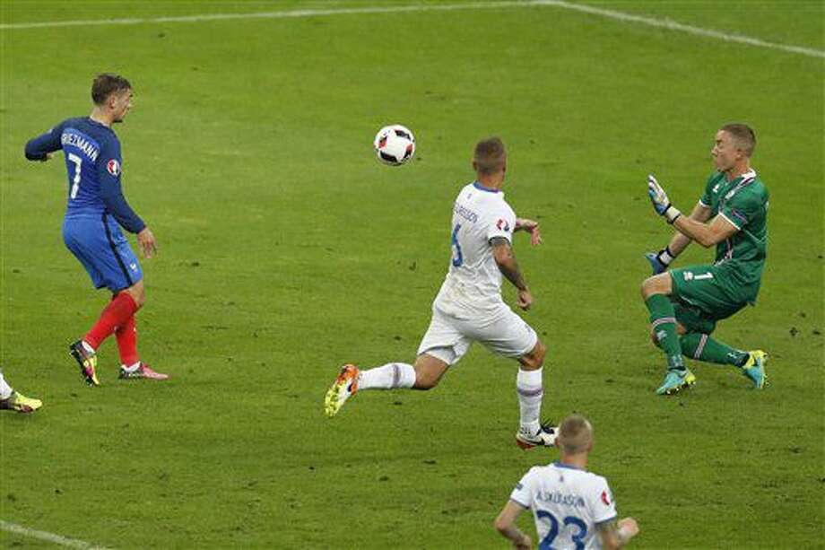 France's Antoine Griezmann, left, kicks to score his side's fourth goal past Iceland goalkeeper Hannes Halldorsson, right, during the Euro 2016 quarterfinal soccer match between France and Iceland, at the Stade de France in Saint-Denis, north of Paris, France, Sunday, July 3, 2016. (AP Photo/Michael Sohn) Photo: Michael Sohn