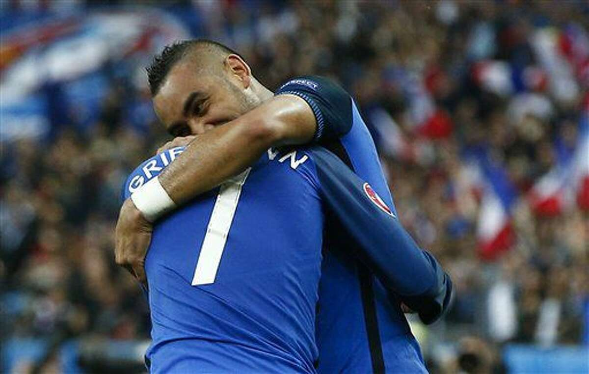 France's Dimitri Payet, right, celebrates with his teammate Antoine Griezmann after scoring his side's third goal during the Euro 2016 quarterfinal soccer match between France and Iceland, at the Stade de France in Saint-Denis, north of Paris, France, Sunday, July 3, 2016. (AP Photo/Thibault Camus)