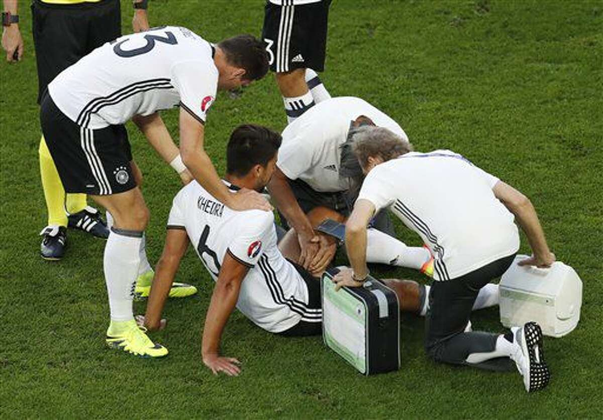 Germany's Sami Khedira gets assistance after getting injured during the Euro 2016 quarterfinal soccer match between Germany and Italy, at the Nouveau Stade in Bordeaux, France, Saturday, July 2, 2016. (AP Photo/Michael Sohn)