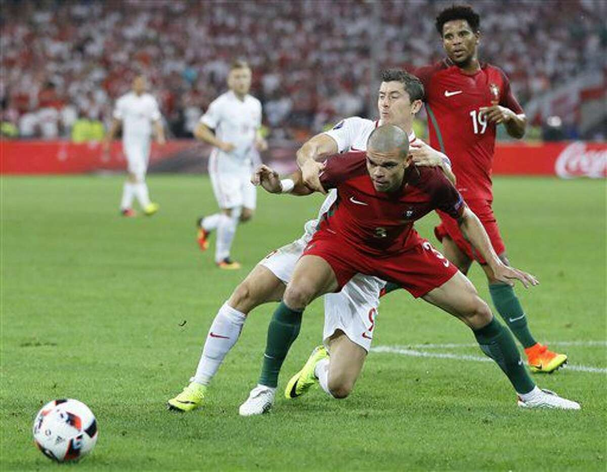 Portugal's Pepe, foreground, holds back Poland's Robert Lewandowski during the Euro 2016 quarterfinal soccer match between Poland and Portugal, at the Velodrome stadium in Marseille, France, Thursday, June 30, 2016. (AP Photo/Frank Augstein)