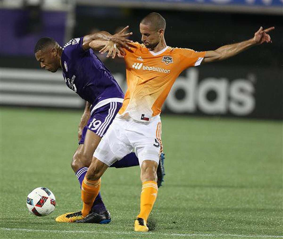 Orlando City's Julio Baptista (19) keeps the ball from Houston player Raul Rodriguez (5) during an MLS soccer game in Orlando, Fla., Friday, July 8, 2016. (Stephen M. Dowell/Orlando Sentinel via AP)