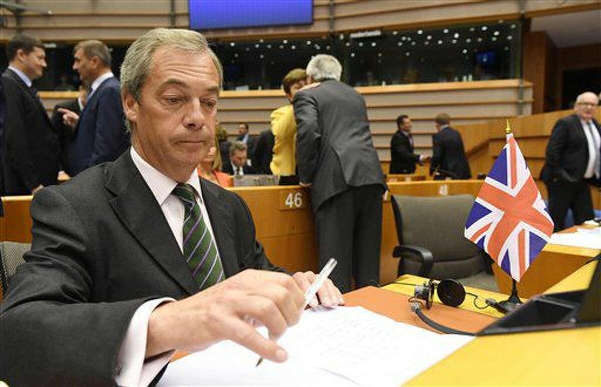 En esta imagen de archivo, tomada el 28 de junio de 2016, el líder del Partido Independentista del Reino Unido (UKIP), Nigel Farage, sentado junto a una bandera británica durante una sesión especial del Parlamento Europeo, en Bruselas. Farage anunció su dimisión el 4 de julio de 2016. (AP Foto /Geert Vanden Wijngaert, archivo)