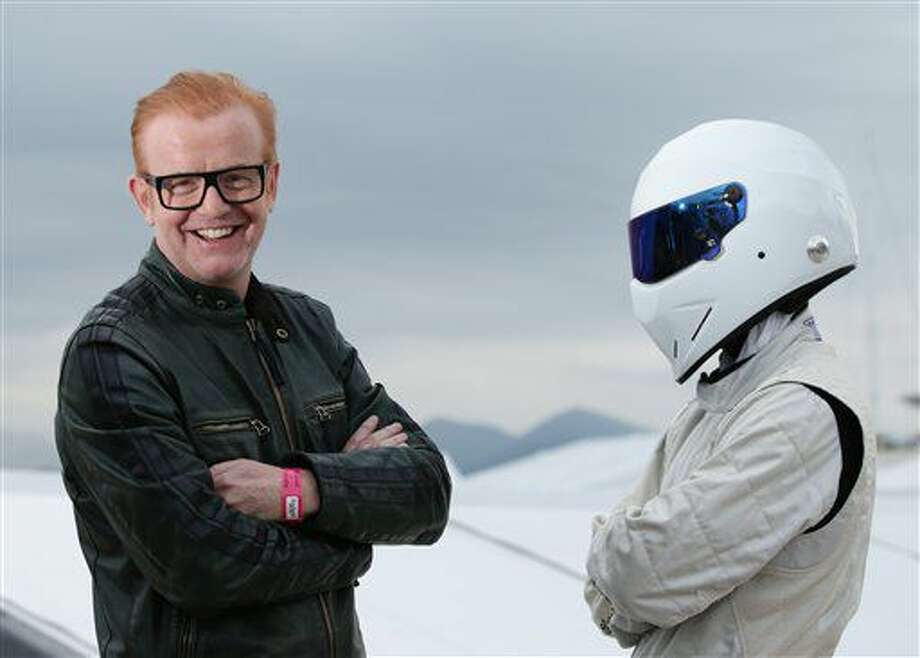 """FILE - An Oct. 6, 2015 photo from files of Chris Evans, left, standing with """"The Stig"""" in Cannes, France. Host Chris Evans has announced Monday July 4, 2016, that he is quitting the BBC's flagship car show """"Top Gear,"""" saying """"standing aside is the single best thing I can do."""" The show has struggled to draw a big audience since it was relaunched in May, hosted by Evans and Matt LeBlanc. The revamped show attracted just 1.9 million viewers to its season finale on Sunday. (Yui Mok/PA File via AP) Photo: Yui Mok"""