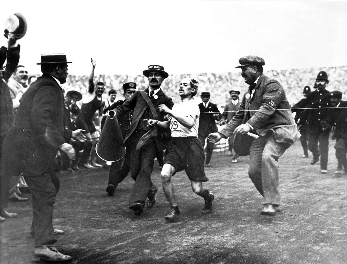 Italian runner Dorando Pietri finishing the marathon first with the help of others and is subsequently disqualified in the 1908 London Summer Olympic Games.