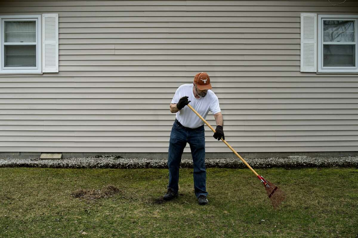 Kim Stadler of Midland rakes up leaves and sticks in his yard in this file photo.