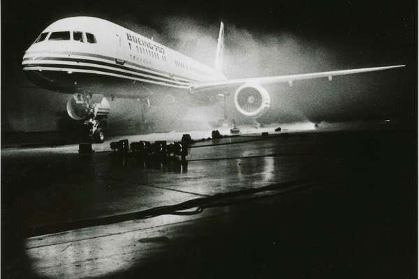 """Original caption (Jan. 12, 1982): """"The Boeing 757 emerged from a mist specially created to lend an eerie effect to yesterday's debut at the Renton plant where the jetliner is assembled. Strobes and flood lights turned the unveiling into a stage spectacular to the delight of the 12,000 Boeing employees, customers, officials and guests who broke in applause as the football-field-sized curtain parted to reveal the new airplane."""" Image number 2000.107.003.30.15."""