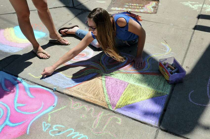 Courtney Dowsey adds her chalk drawing to sidewalk art project during Art on Lark on Saturday, June 6, 2015, in Albany, N.Y. (Cindy Schultz / Times Union)