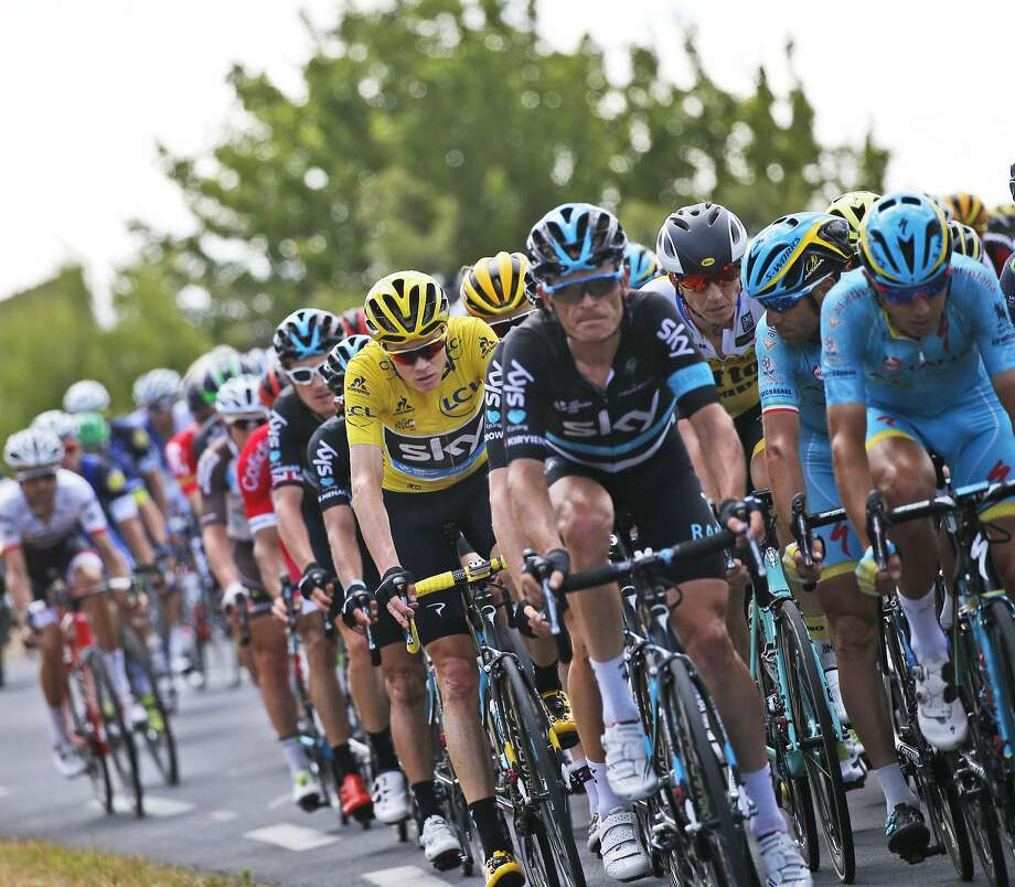 Chris Froome, wearing the overall leader's yellow jersey, rides in the pack during the Wednesday's Stage 11. Photo: Christophe Ena, Associated Press