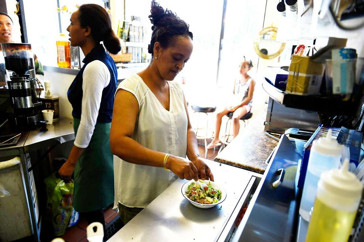 Nigisty Eyasu prepares a tuna salad dish on Tuesday, July 12, 2016 at Alem's Coffee in Oakland, California.