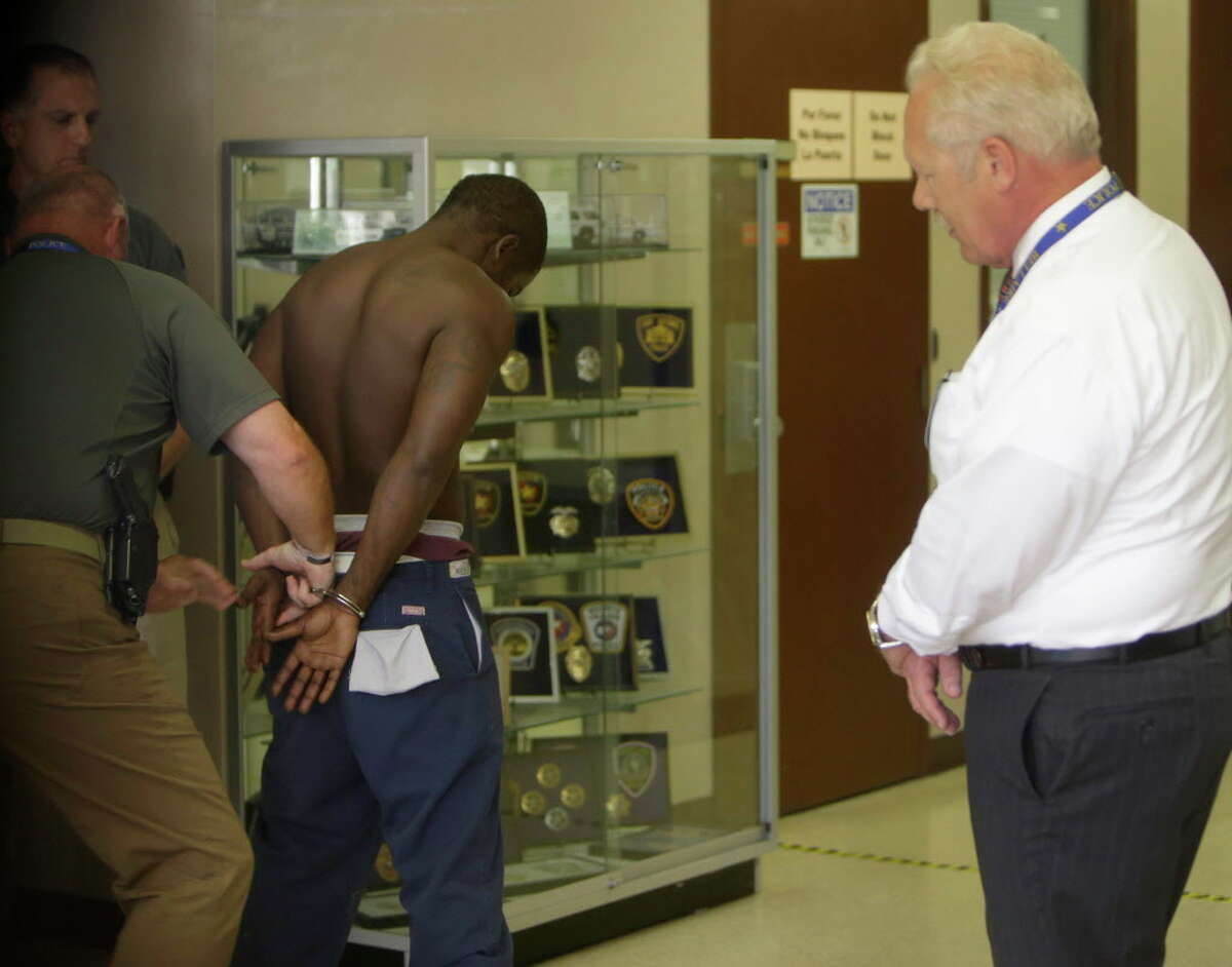 Bellaire Police Chief Byron Holloway, right, watches as Dante Moore is put into handcuffs inside the Bellaire Police Department, 5110 Jessamine St., Wednesday, July 13, 2016. Moore, a person of interest in the death of Officer Marco Zarate, was escorted to the police station by Quanell X.
