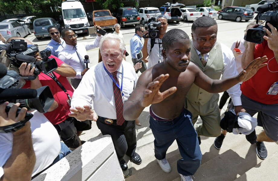 Bellaire Police Chief Byron Holloway, left,  takes Dante Moore, center, escorted by Quanell X, right, into custody at the Bellaire Police Dept., 5110 Jessamine St., Wednesday, July 13, 2016, in Houston. He is a person of interest in the death of a Bellaire police officer, Marco Zarateone. Photo: Melissa Phillip, Houston Chronicle / © 2016 Houston Chronicle
