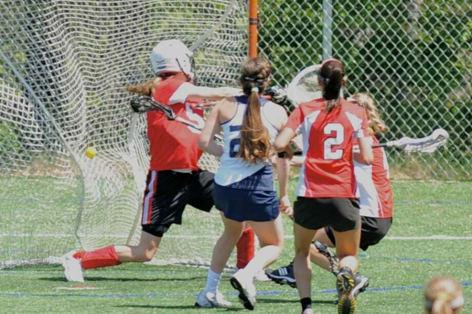 Staples sophomore Remy Nolaan scores a goal against Greenwich on Saturday in a 12-4 loss. Nolan was tenacious all game with four ground balls, four forced turnovers, one interception and two draw controls. Photo: Contributed Photo / Scott Seo