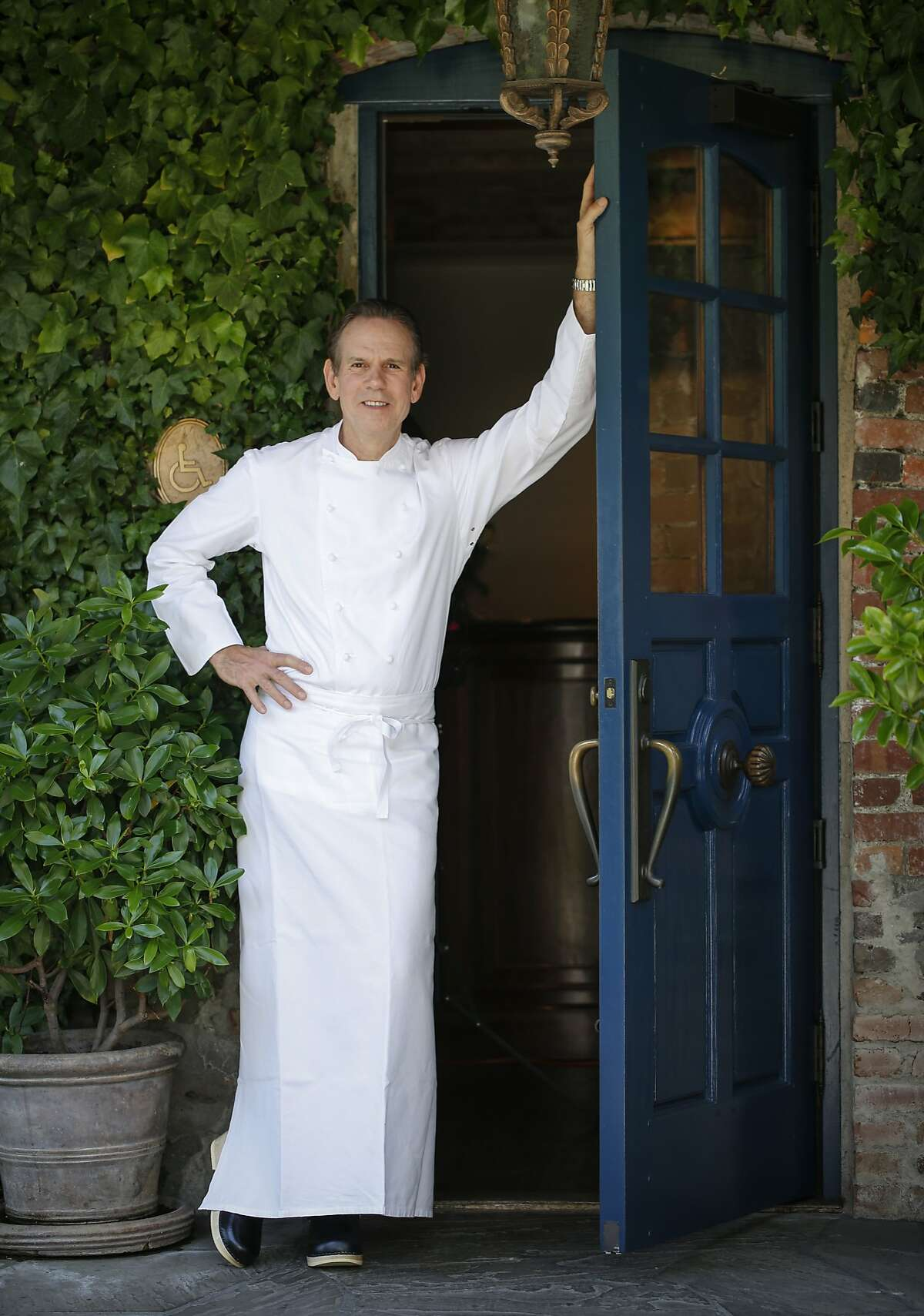 Chef Thomas Keller stands in the doorway of The French Laundry on Wednesday, April 16, 2014 in Yountville, Calif. The renowned chef recently purchased a property in Napa, near his award-winning restaurant. Click through the gallery to see photos of the 2-acre property.