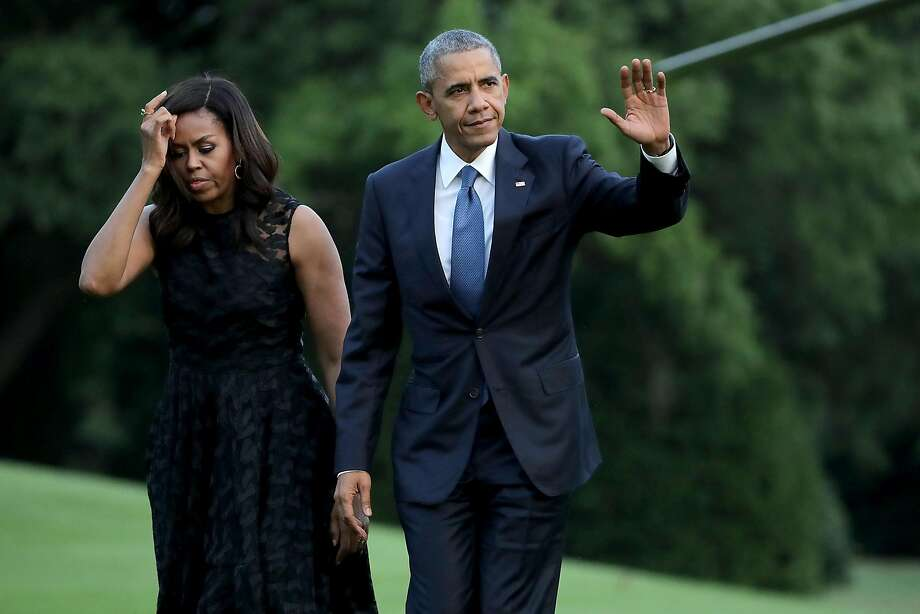 WASHINGTON, DC - JULY 12:  (AFP OUT) U.S. President Barack Obama (R) and first lady Michelle Obama walk across the South Lawn after returning to the White House on Marine One July 12, 2016 in Washington, DC. The Obamas were returning from Dallas where they attended a public memorial service for the five Dallas police officers who were killed by a sniper last week during a Black Lives Matter demonstration.  (Photo by Chip Somodevilla/Getty Images) Photo: Chip Somodevilla, Getty Images