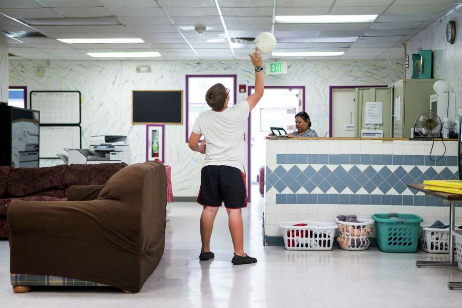 A resident of the Tejano Center for Community Concerns Emergency Shelter flips a ball in the air as he hangs out in the day room at the facility on Tuesday, July 12, 2016, in Houston. The emergency shelter stands at the site that city council is considering allocating $3.5 million in federal grants to help build an affordable housing complex geared toward youth aging out of foster care. Photo: Brett Coomer, Houston Chronicle / © 2016 Houston Chronicle