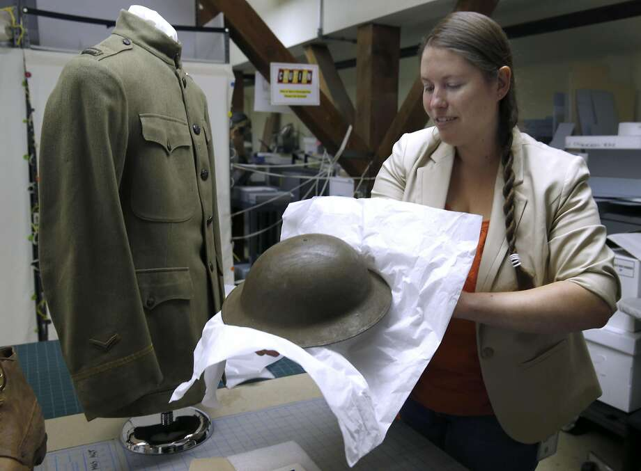 Amanda Williford, curator of the GGNRA museum, prepares a World War I soldier's uniform that will be on display along with gas masks at the park museum's free annual open house for the public on Sunday and Monday. Photo: Paul Chinn, The Chronicle