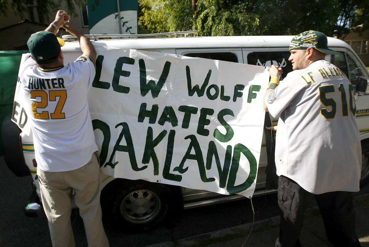 Jorge Leon (left) and Bobby Tselentis hang a banner critical of Oakland A's owner Lew Wolff outside a community meeting at Peralta Elementary School to discuss ballpark options in Oakland in 2010.